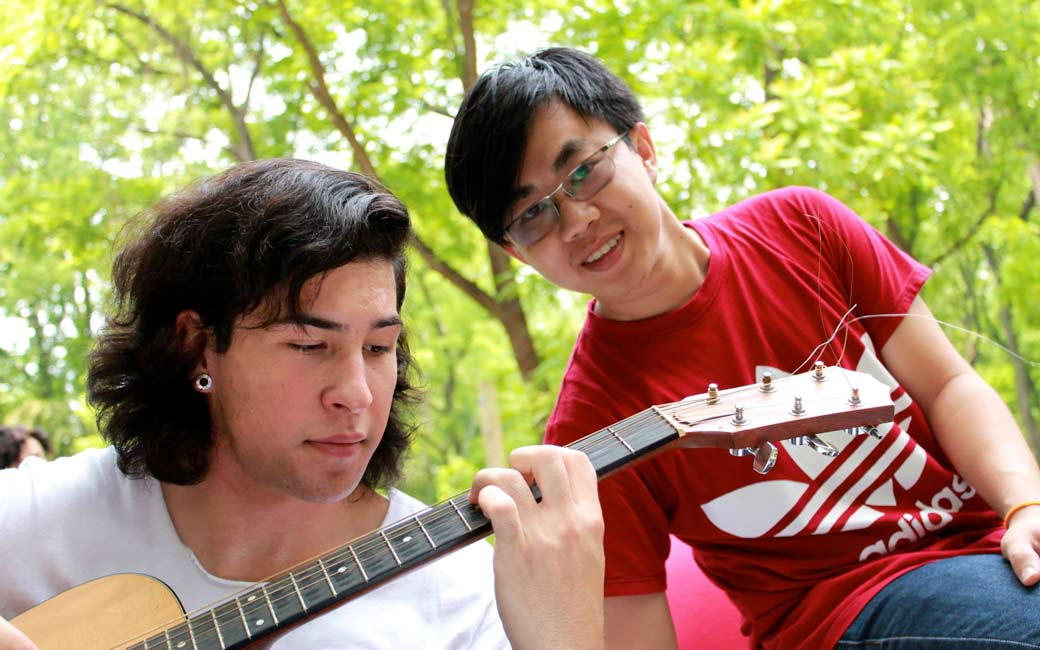 two students, one playing the guitar