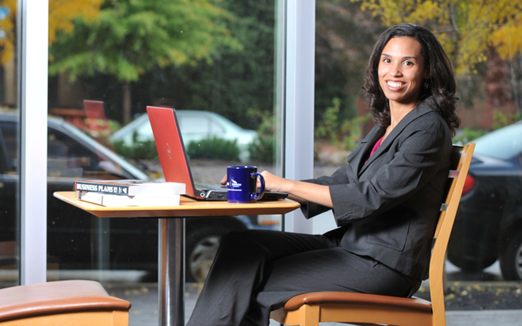 Graduate Student sitting at a table with laptop