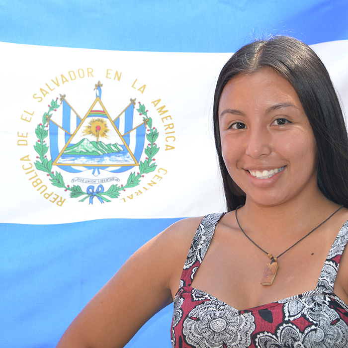 student in front of flag of el salvador