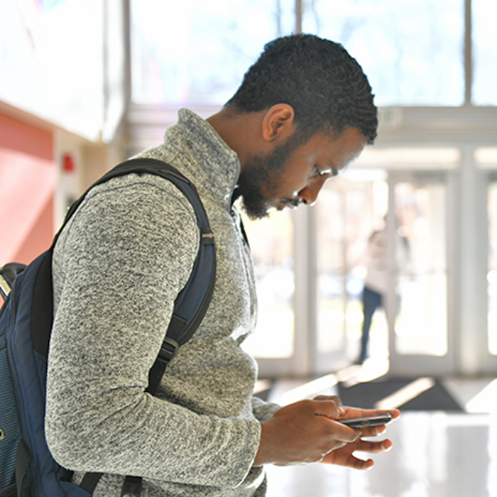male student reading smartphone screen