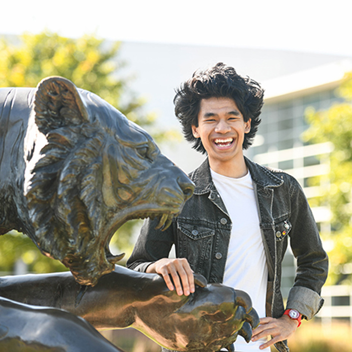 smiling male student posing beside the tiger statue