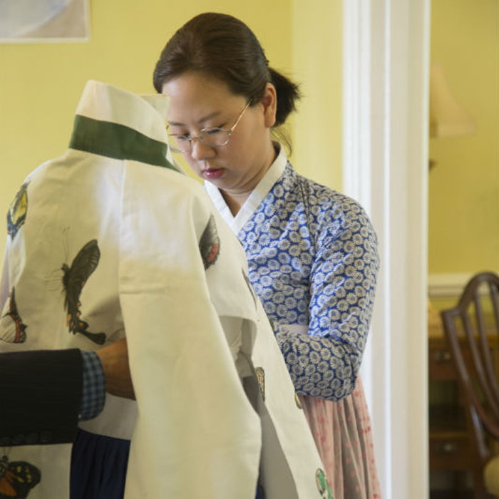 Korean artist Abby Song readies one of her hanboks for display.