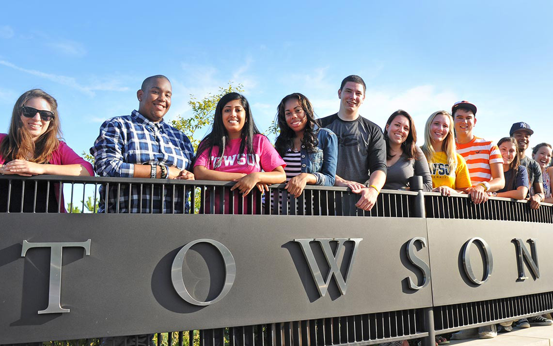 Diverse population of Towson University students standing at TU entrance sign