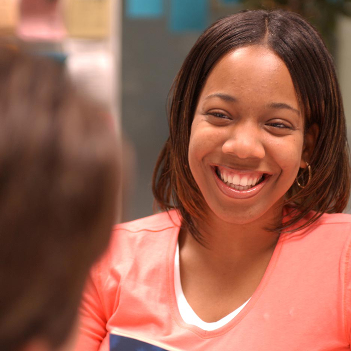 Student smiling greeting guest at Career Center