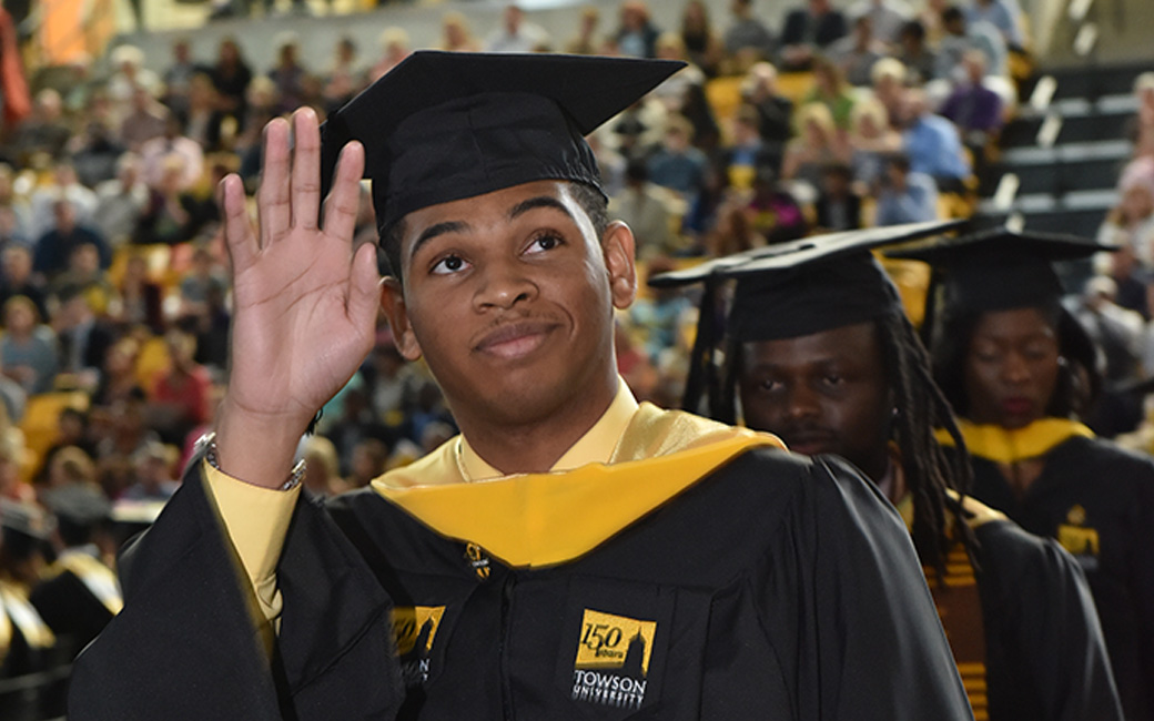 TU student waiving to crowd at graduation