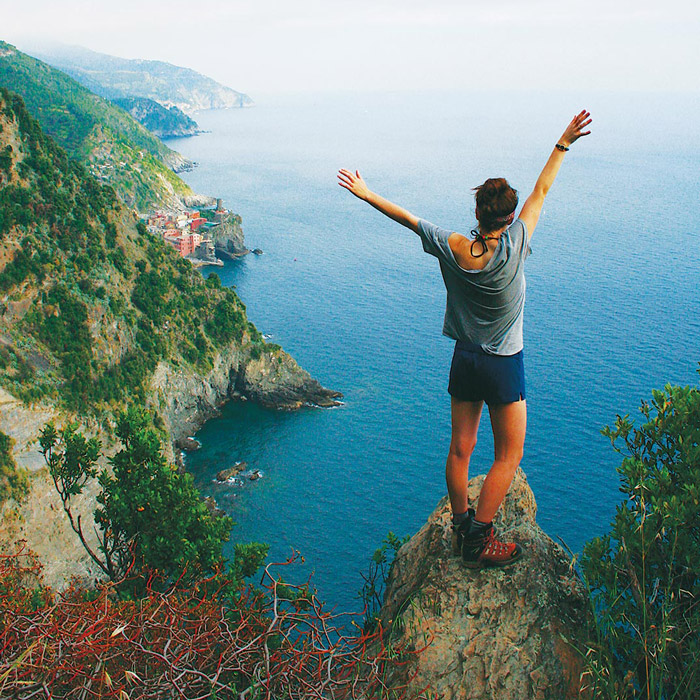 International student with arms raised overlooking scenic cliff