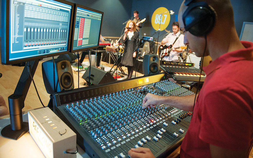Student intern at radio station sound board with band in background