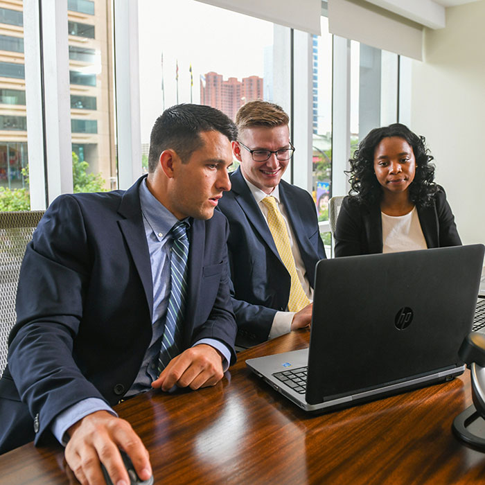 Three students working at a latptop at their internship in downtown baltimore