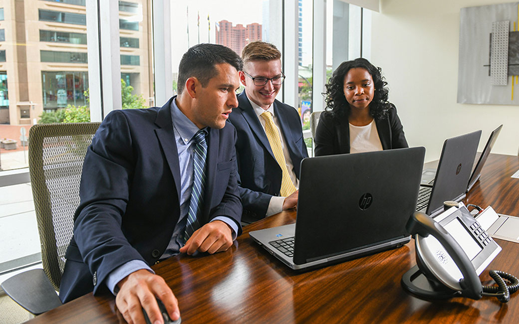 Three Towson University acocunting students working in a conference room overlooking Baltimore's inner harbor at their internship.