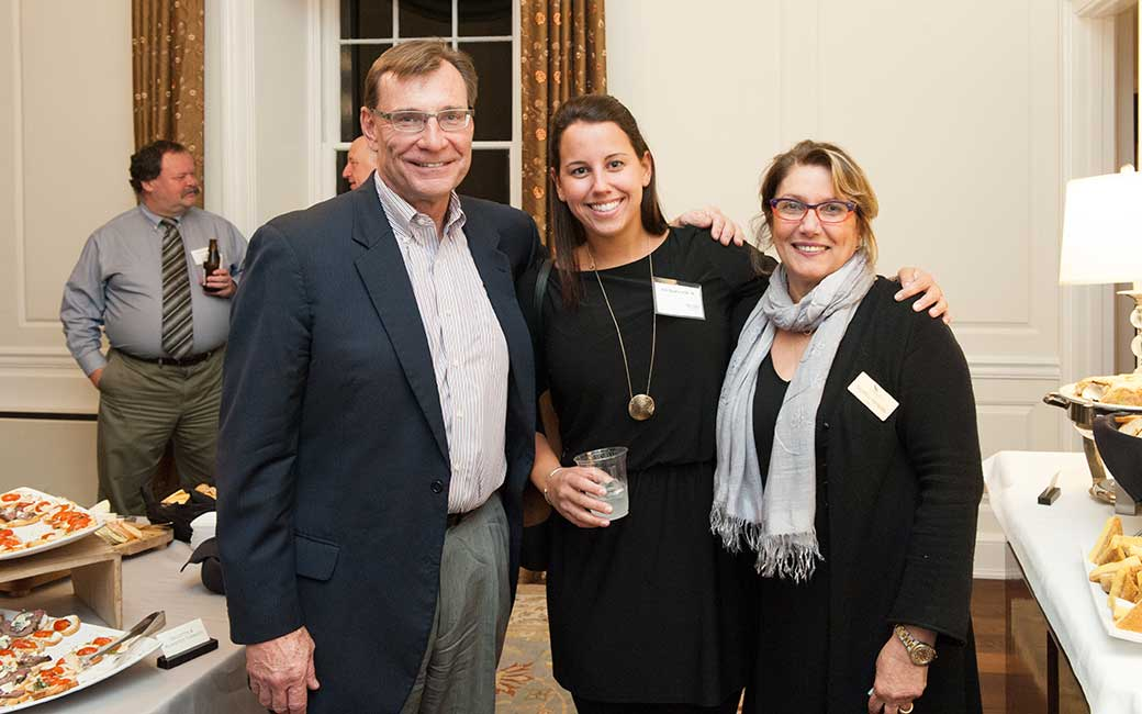two alums with the dean at a networking event