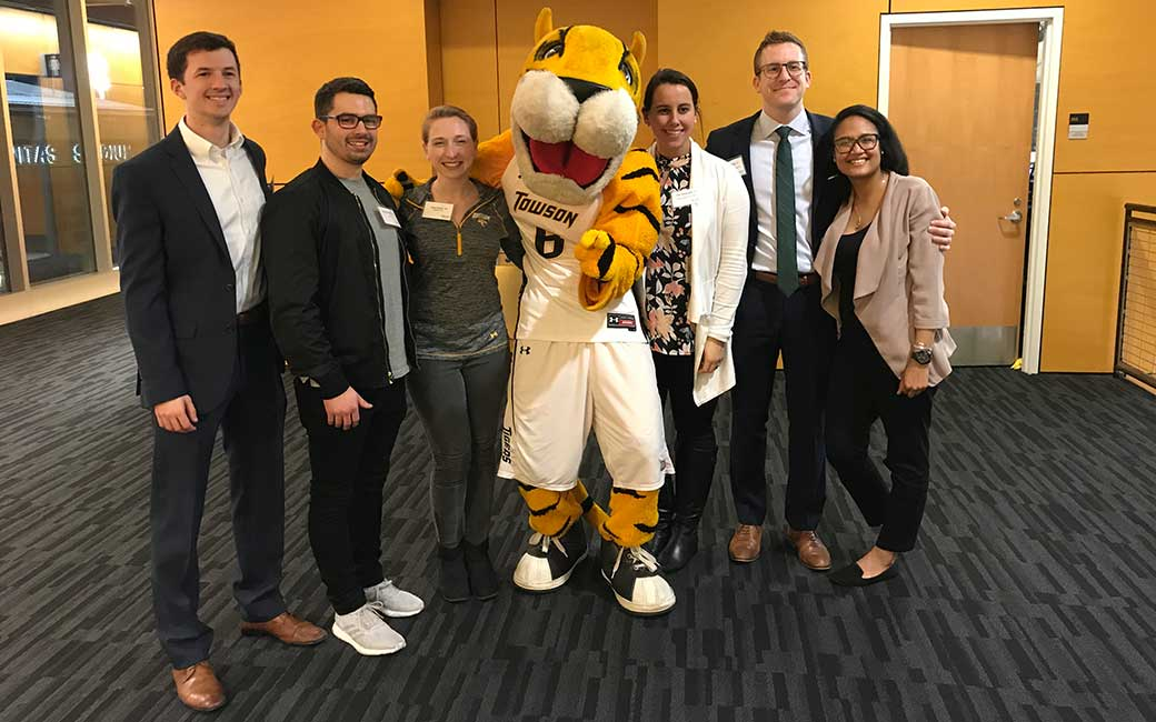 Young alumni posing with Doc the Tiger at one of the TU men's basketball games