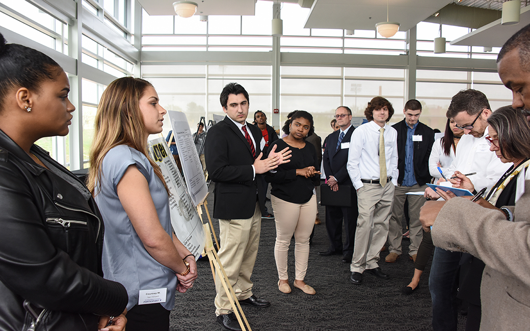 entrepreneurship students deliver a pitch during a poster competition