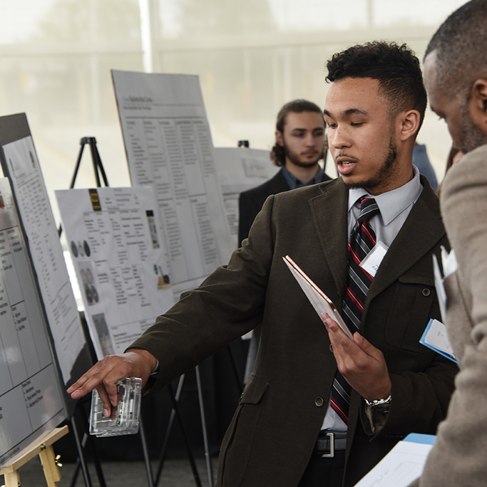 Student showing poster to a judge