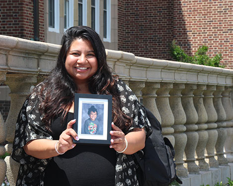 linda ochoa holding a framed portrait of her young son