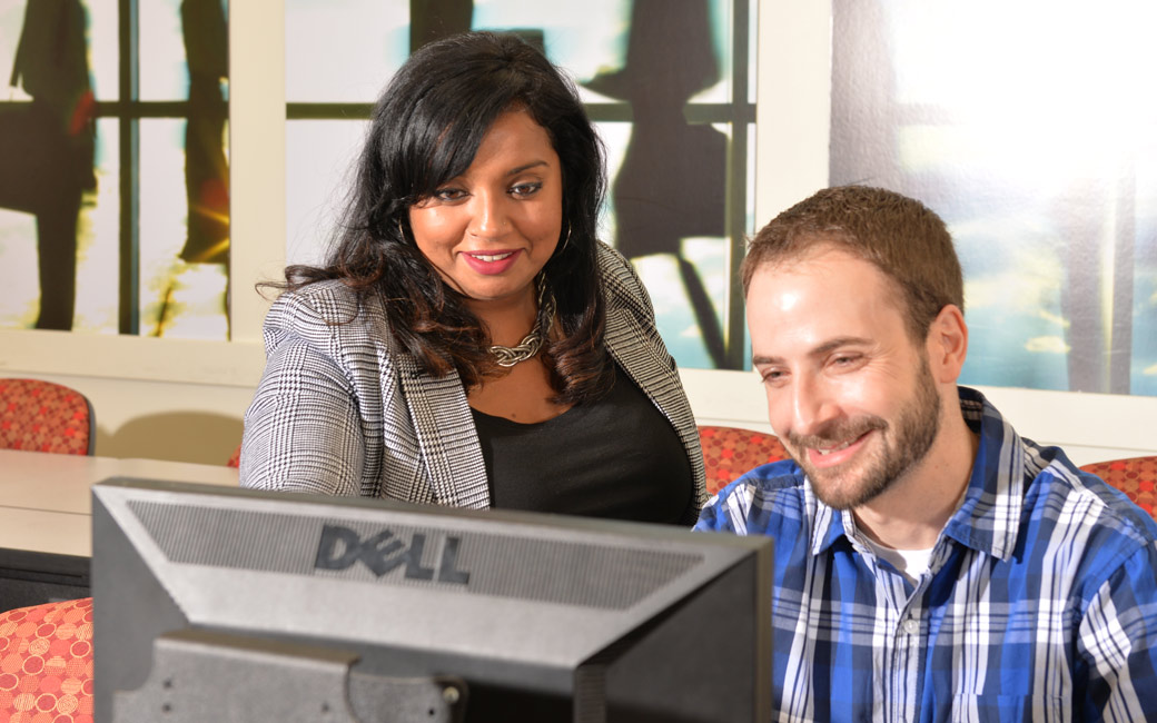 Stella Tomasi instructs a supply chain management master's student at a computer station in the supply chain innovation lab