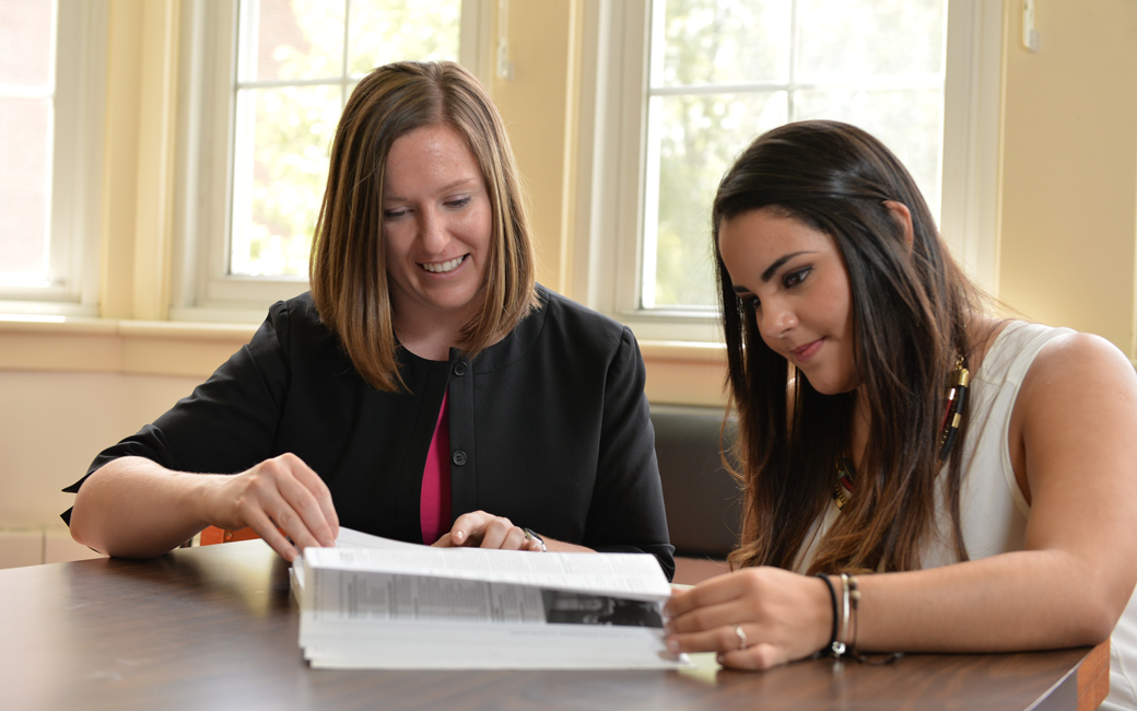 student academic and career services adviser helps a cbe student
