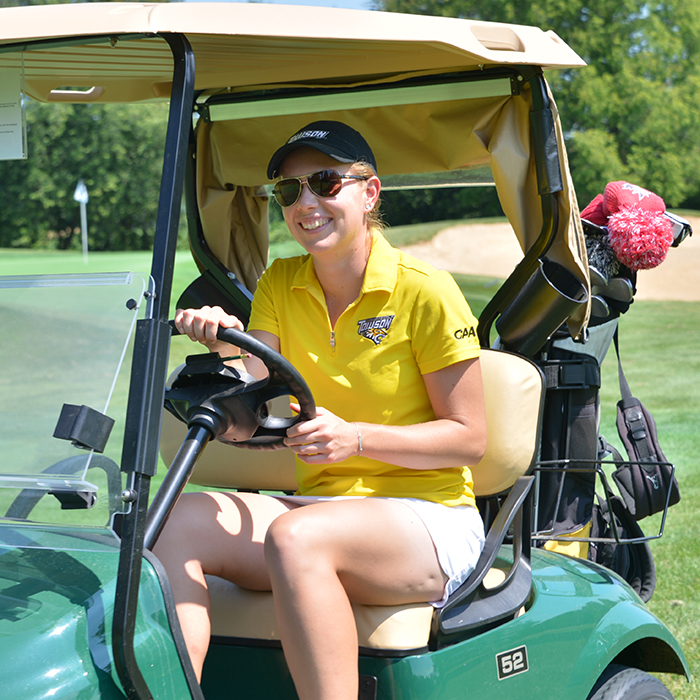 Mackenzie Rice, a women's golf team member and economics student, drives a golf cart