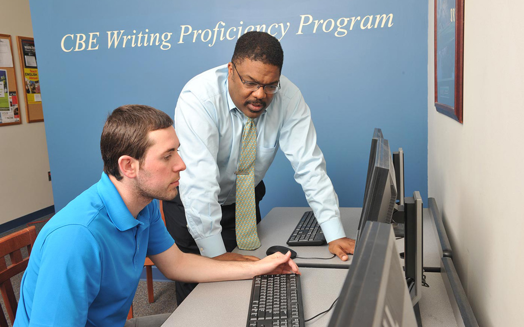 Professor helps a towson university college of business and economics student with a writing assignment in the CBE Writing Lab