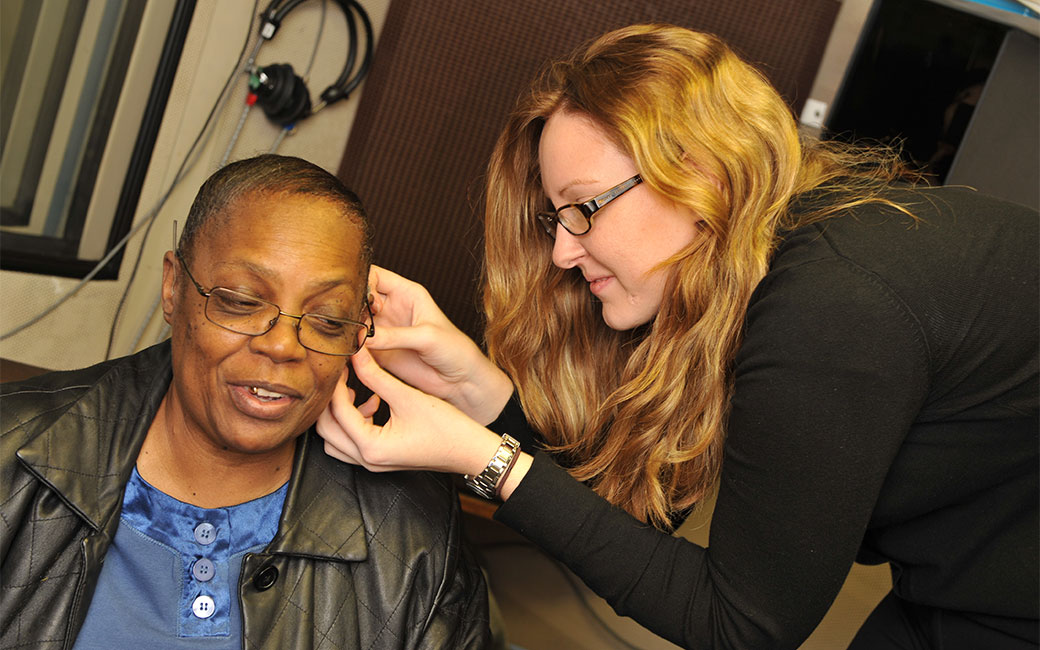 Audiology faculty fits a hearing aid on a person in a lab