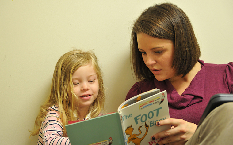 TU student helping young child learn to read