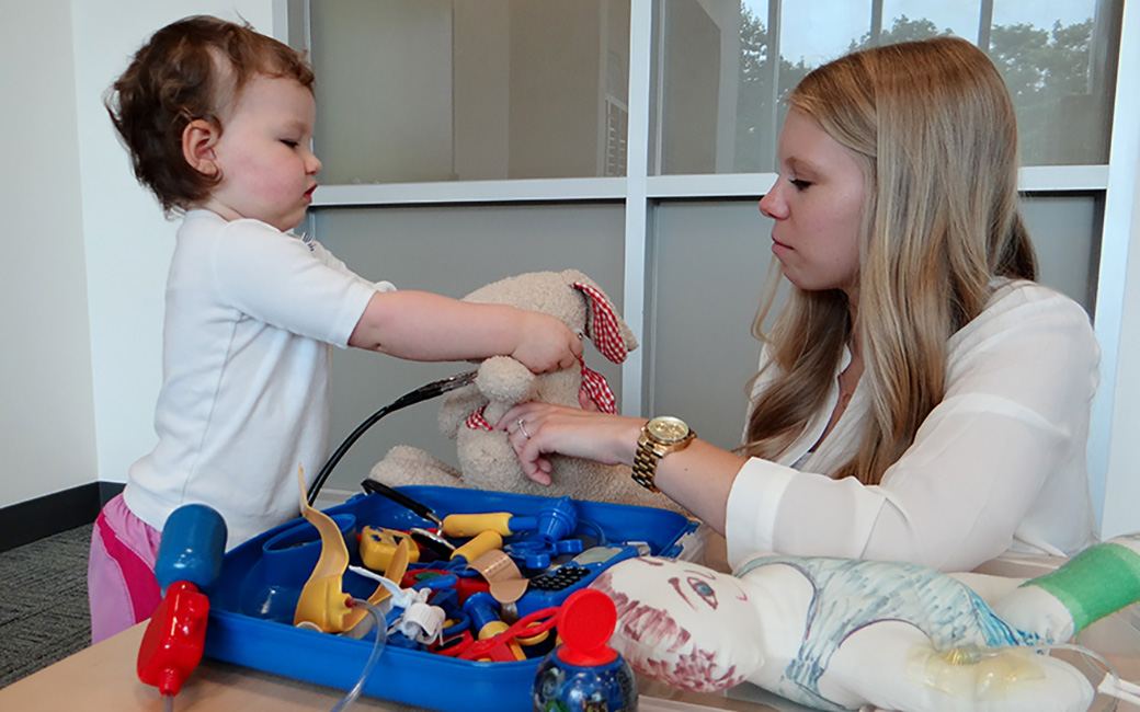Child life student playing with young patient