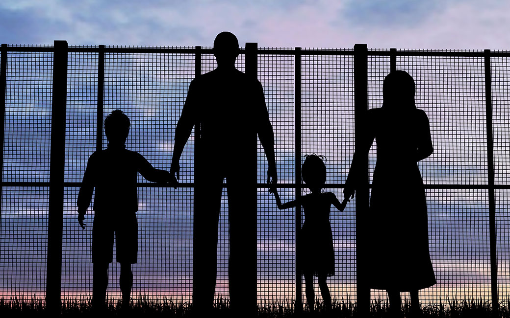 family in silouette in front of a fence