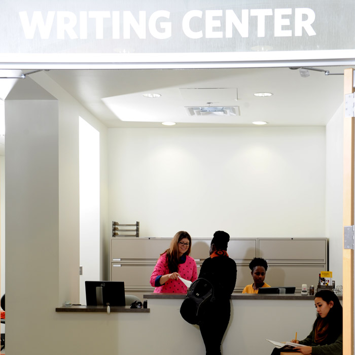 Jessica Reyes, Assistant Director, and students at the main entrance of the CLA Writing Center