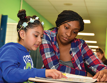 TU intern Kori Harris practices reading with one of her students.