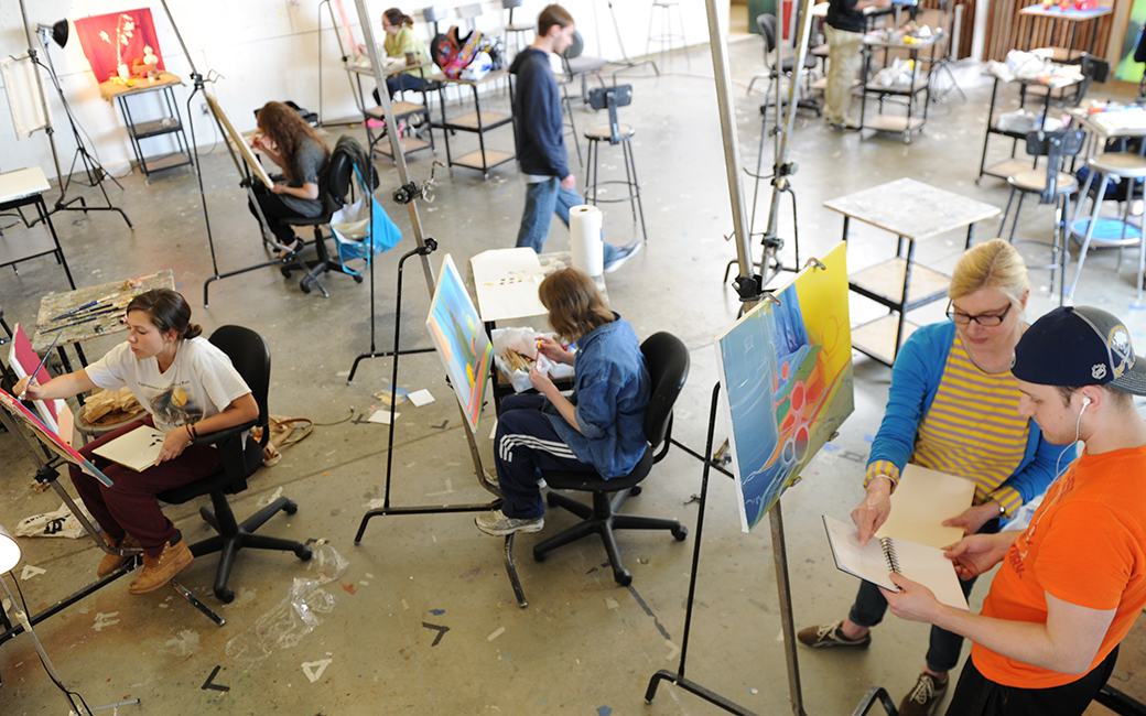 overhead view of students in painting studio standing and sitting at their easels