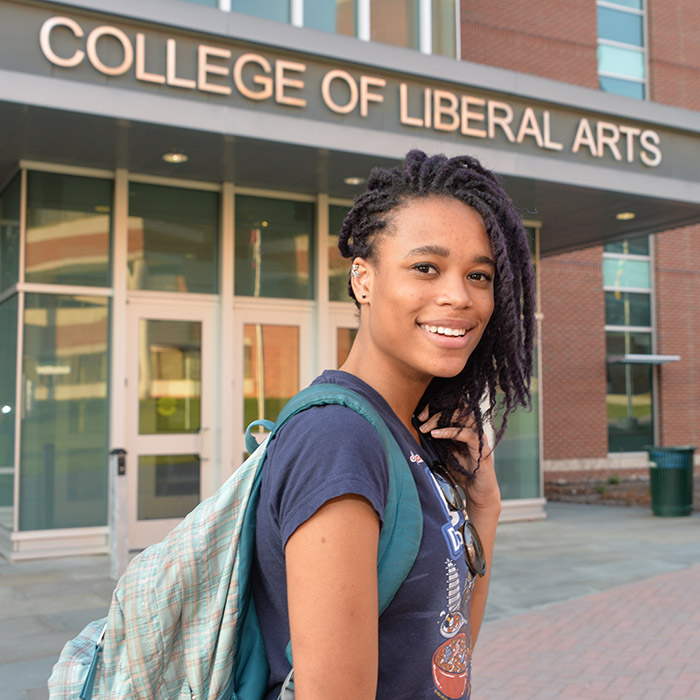 TU student standing in front of the College of Liberal Arts building