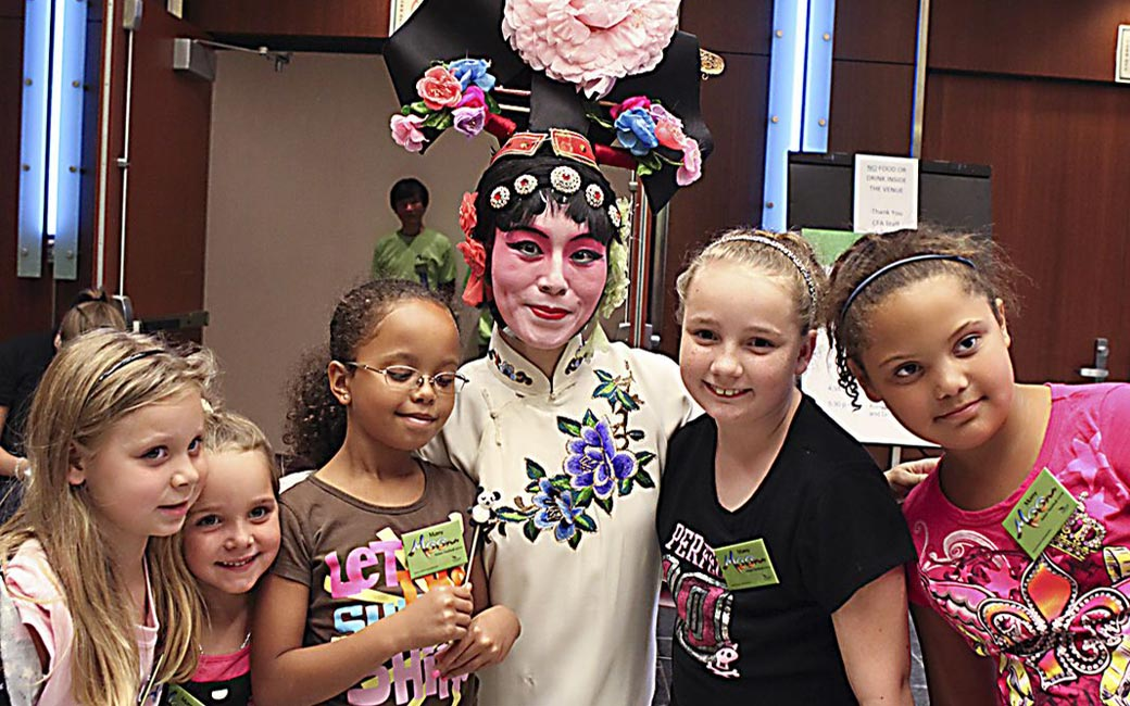 Children with a performer at the Asian Arts and Culture Center's Many Moons Festival in 2010
