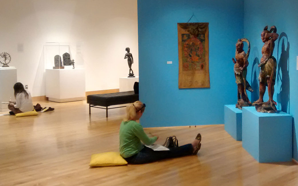 Students study objects on display during the Meditation Exhibition in the Asian Arts Gallery, Fall 2014.