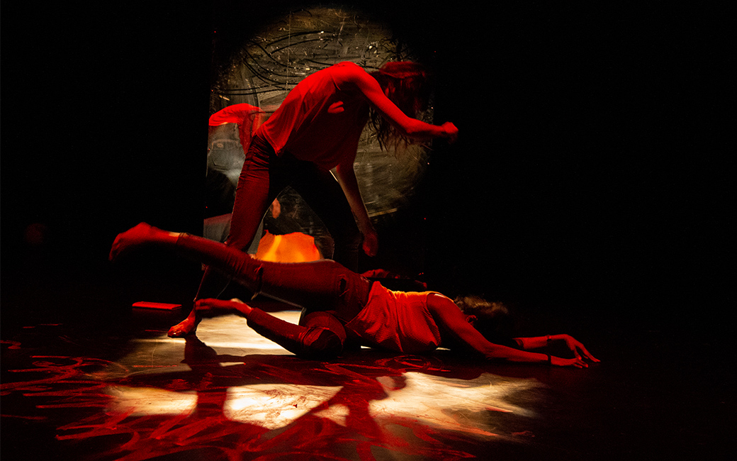Two women performing a theatre piece under dark red light