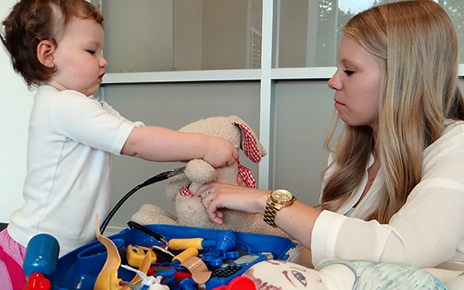 Toddler putting a stethoscope on a stuffed rabbit