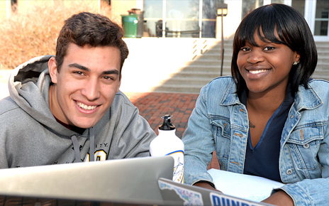Two seated towson students smiling at the camera