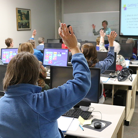 Over-the-shoulder photo of woman raising her hand in a computer lab classroom