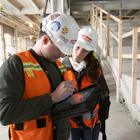 Male and Female construction workers in hardhats viewing a tablet on job site