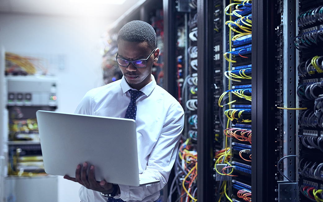 African-American man working on a laptop in a server room