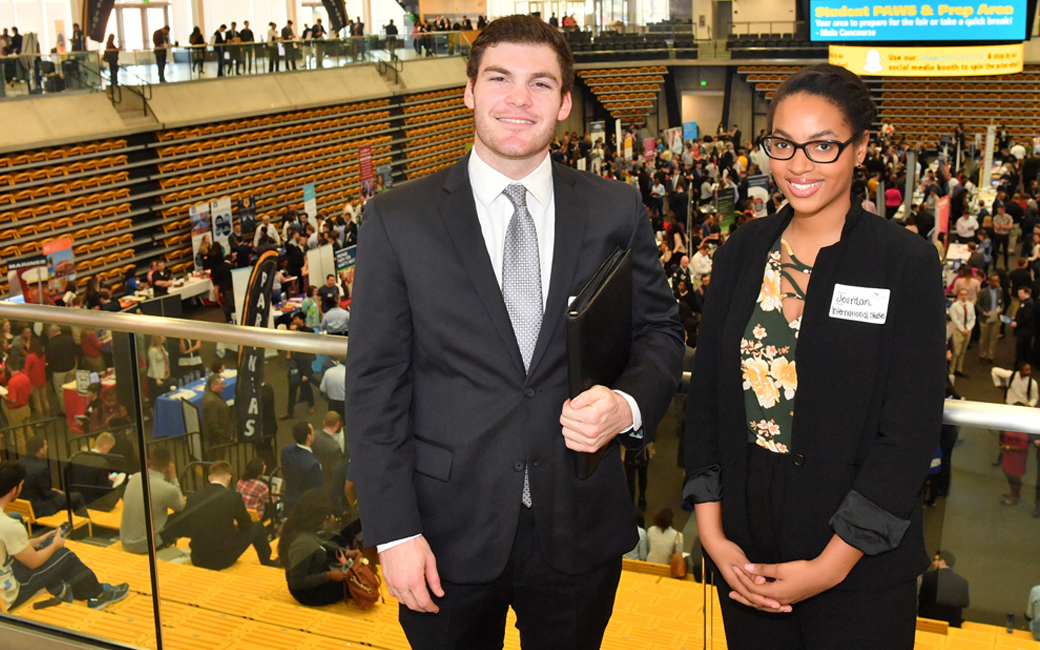 Two towson students in front of Career Fair smiling at the camera