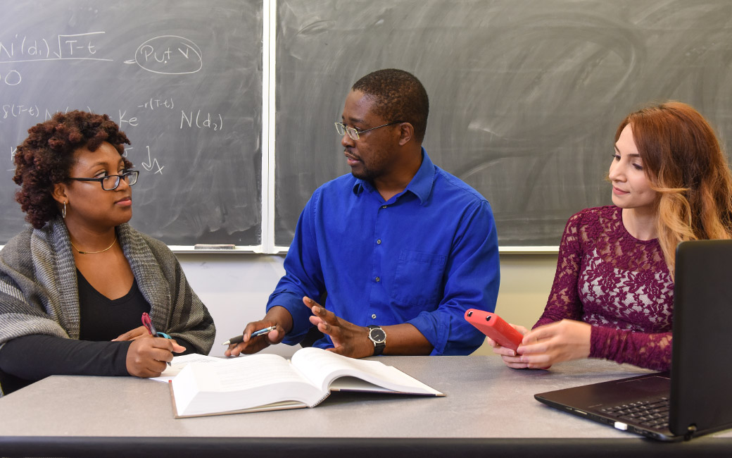 Graduate students discuss math with Professor Pemy