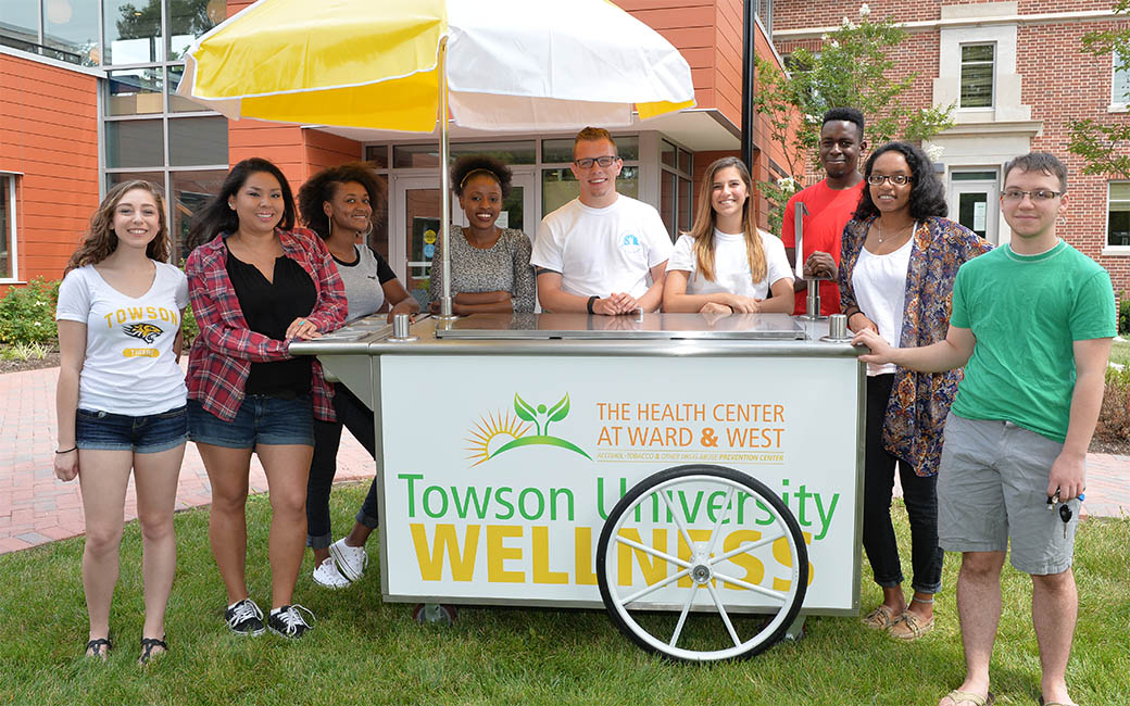 Students standing around a wellness cart