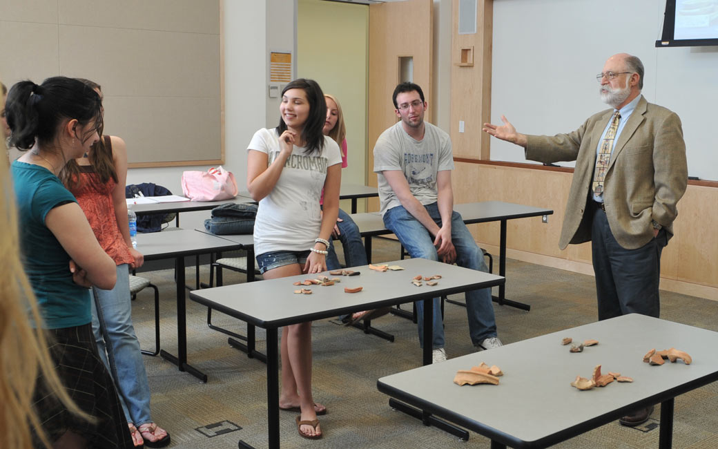 Honors professor leads archaeology class, gesturing to bones arranged on a table as students look on