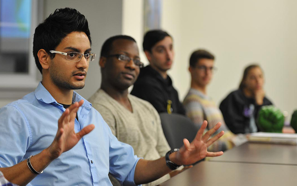 Small, diverse group of students seated at a table during a seminar class as one leads discussion