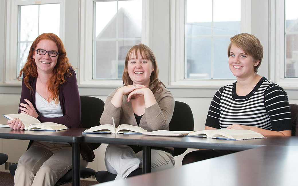 Three female students smiling in a classroom