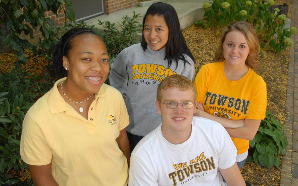 Four students wearing Towson University attire looking at the camera