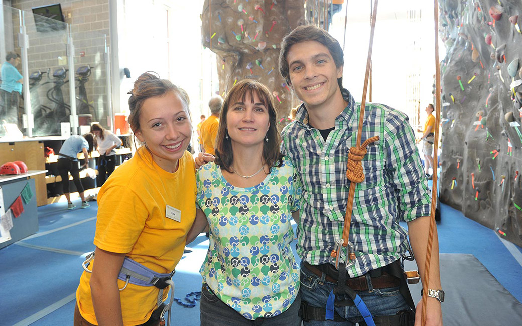 Parent, student, and student worker standing in gym in front of rock climbing wall