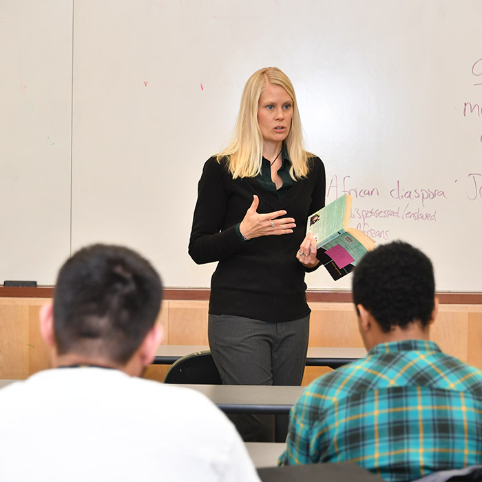 Female faculty member standing in front of a whiteboard deliving a lecture