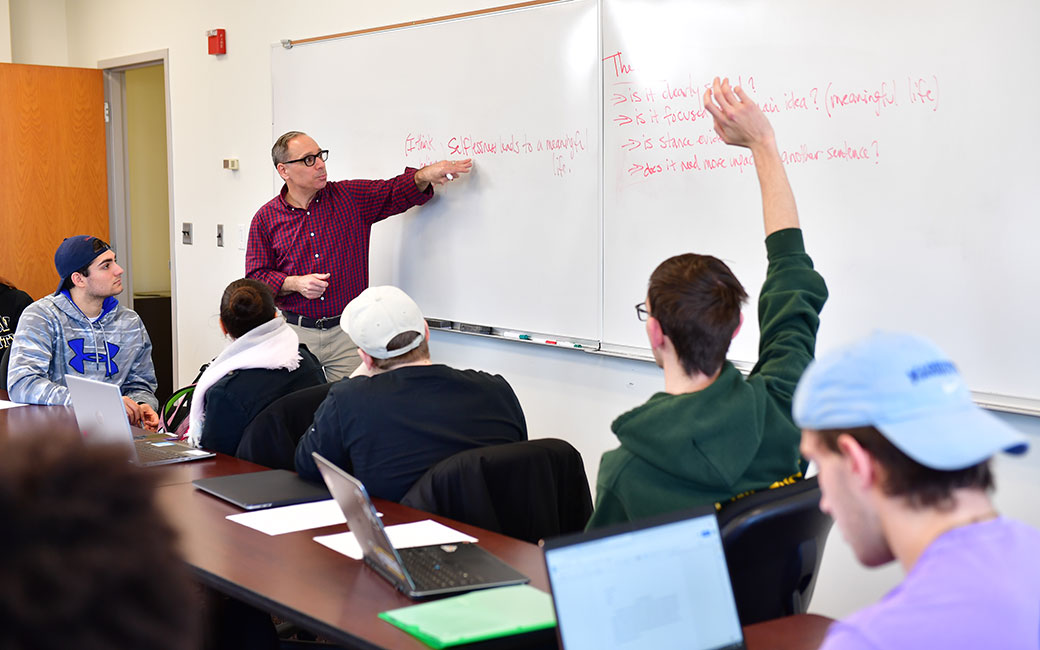 Class meeting in a classroom, with a professor speaking to students seated and raising hands