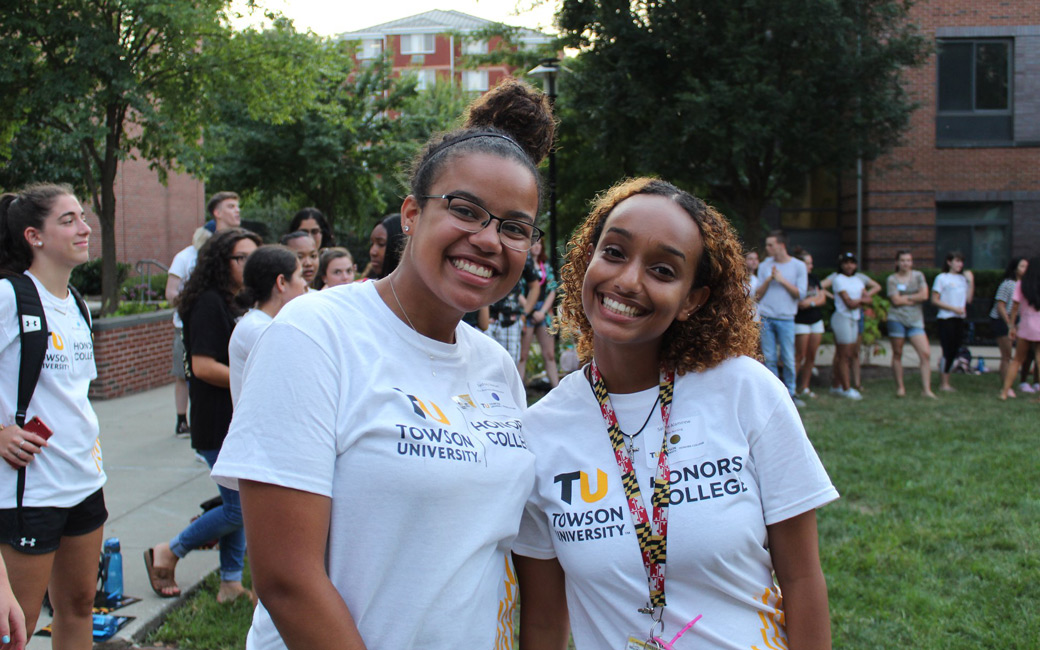 Two Honors Orientation Mentors smiling in front of Orientation participants