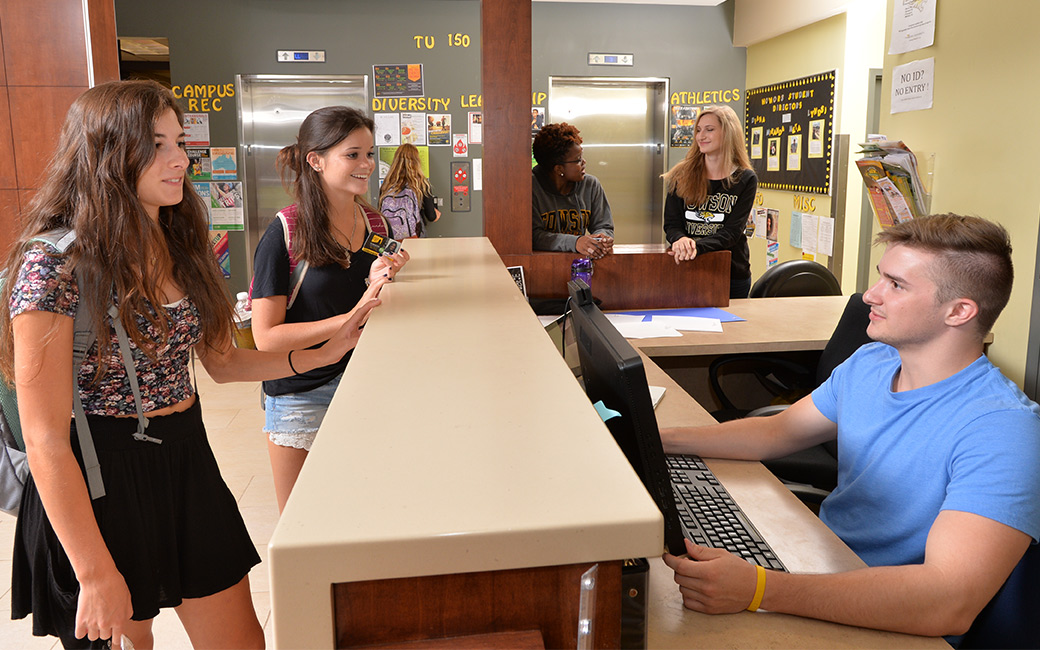 Male student at residence hall front desk greets two students approaching the desk